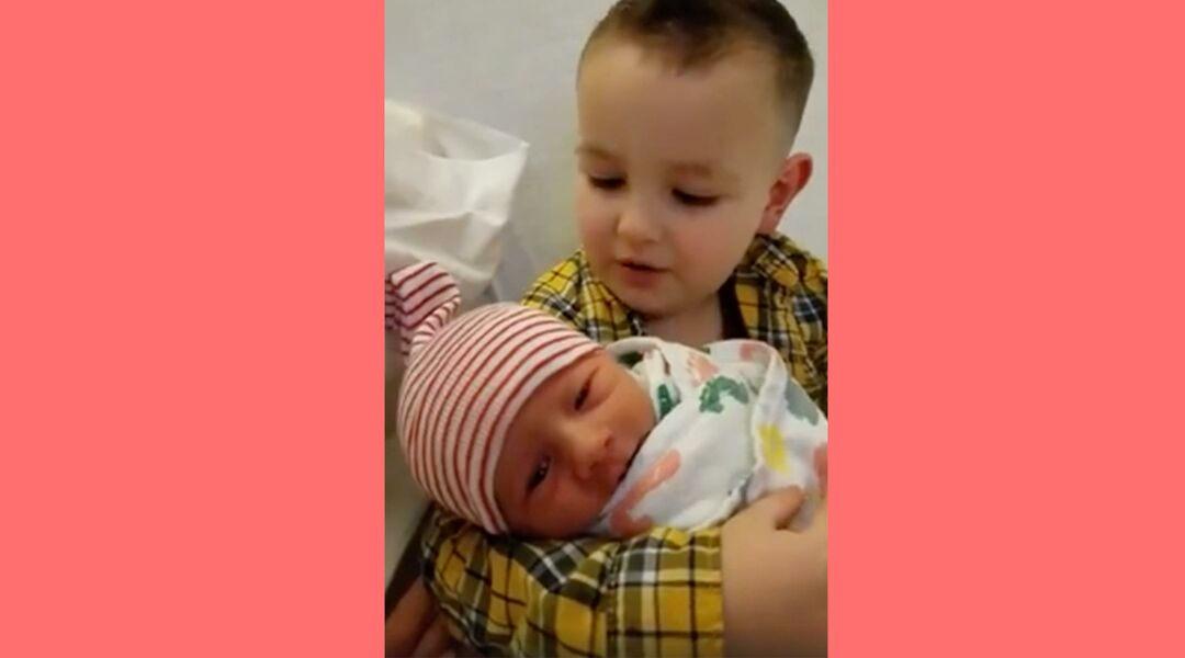 Little boy holding newborn baby brother