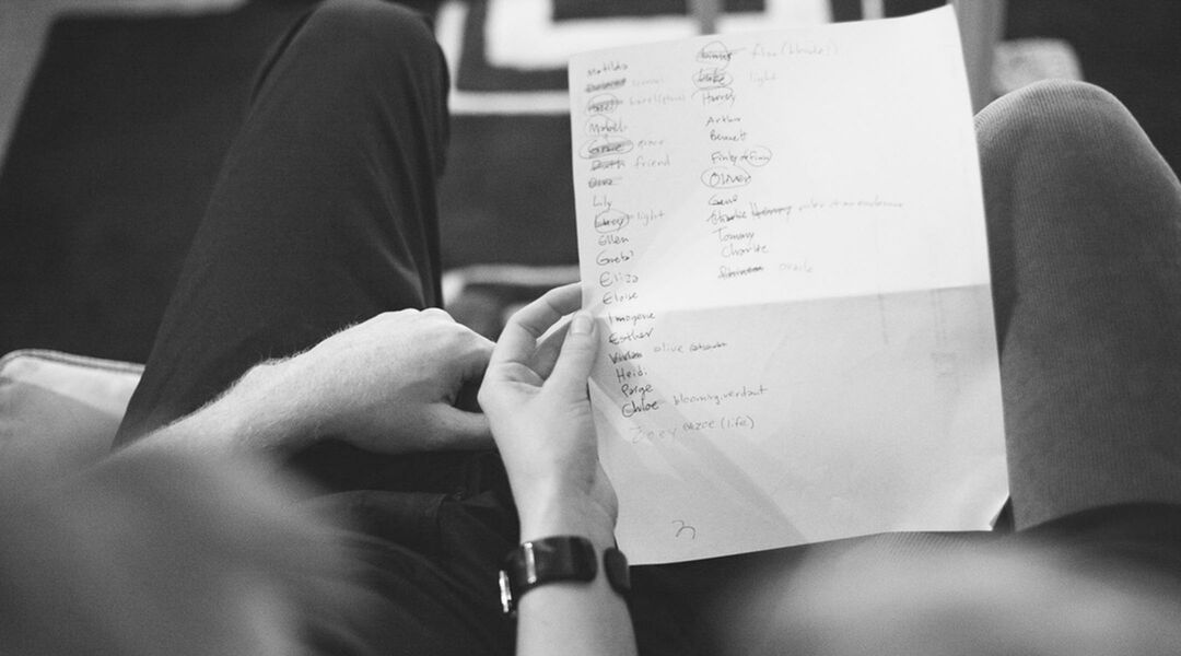 Black and white photo of couple holding a list of baby name ideas