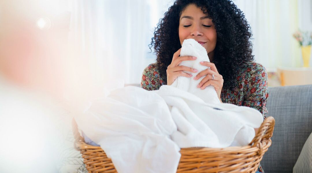 Woman smiling and smelling clean laundry at home.