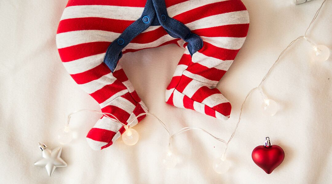 Christmas lights draped over the legs of a baby wearing red and white striped pajamas