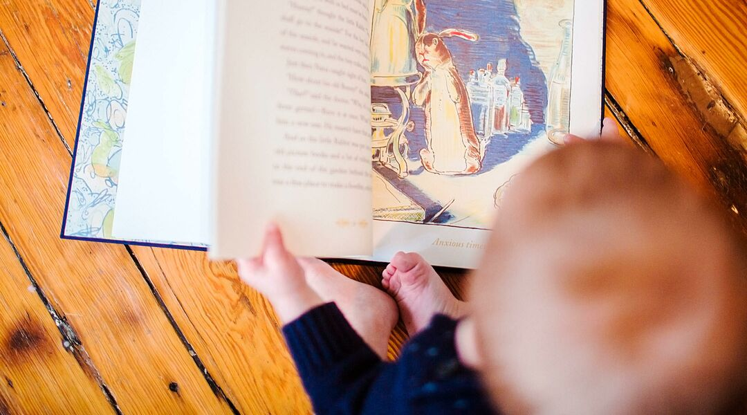 Baby reading rabbit book on his first birthday