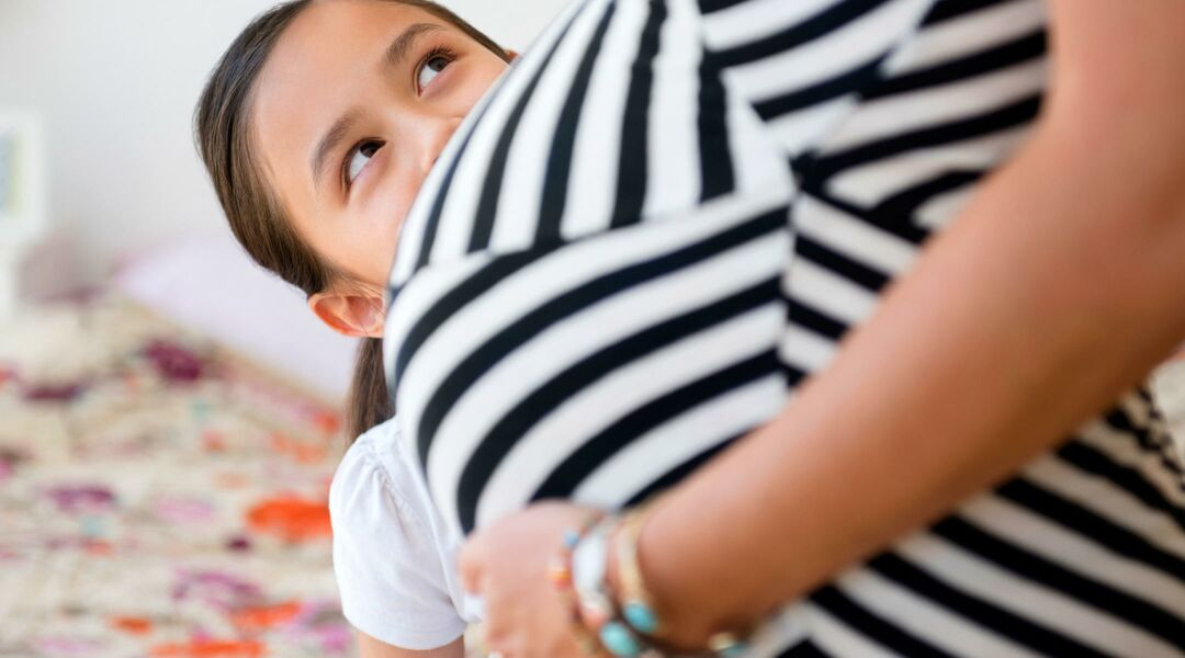 Pregnant woman standing with her older child peering at her pregnant stomach.