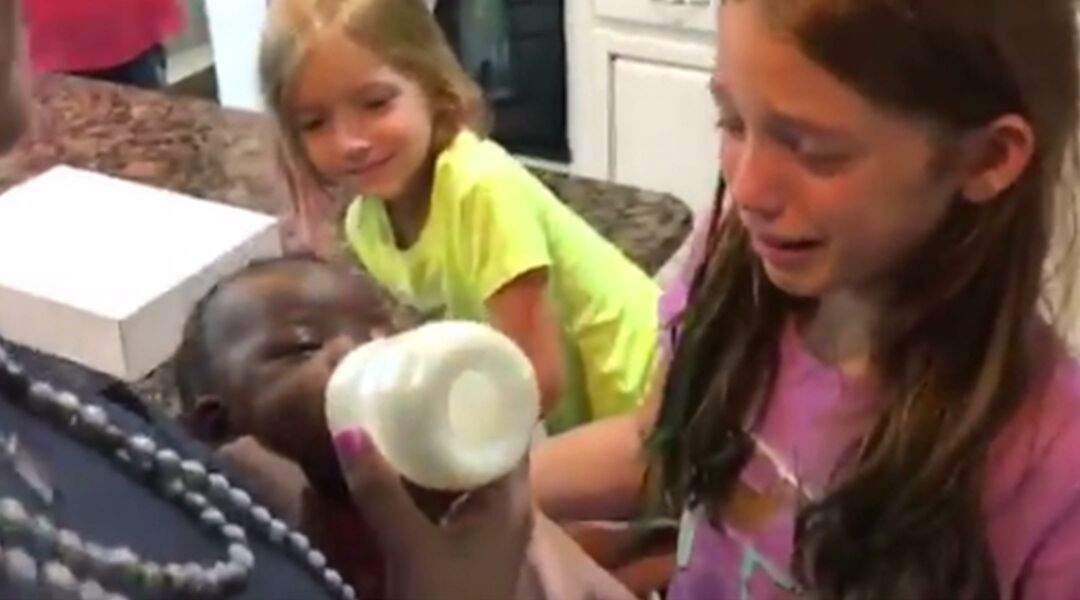Young girls meeting their new baby sister for the first time
