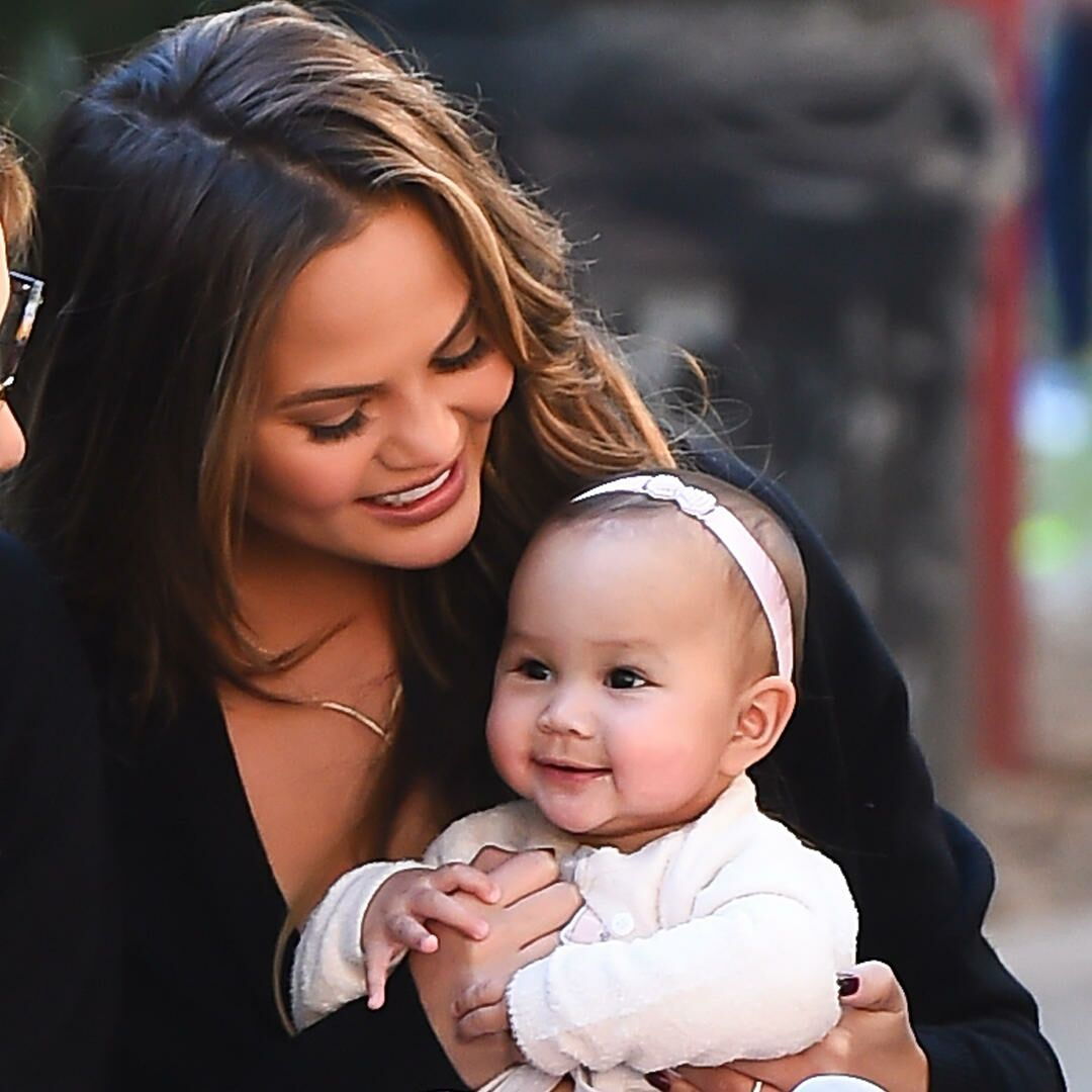Chrissy Teigen holding daughter Luna up outside with friends.
