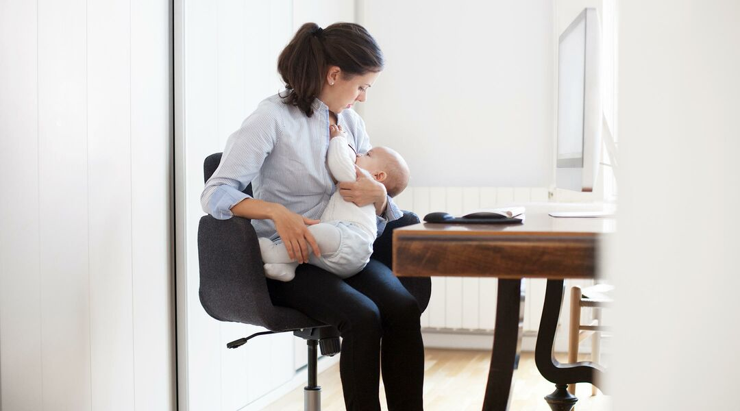 Woman nursing her baby in front of a computer