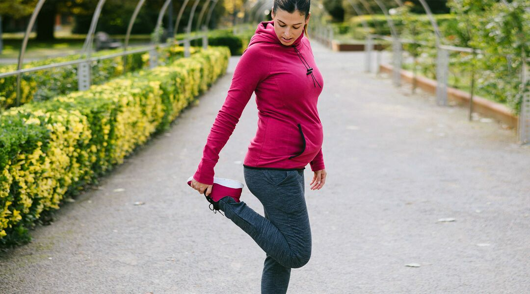 pregnant woman stretching park
