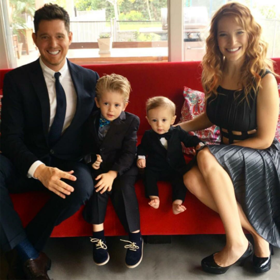 Michael Buble and his wife sitting on a couch in formal attire with two young sons.