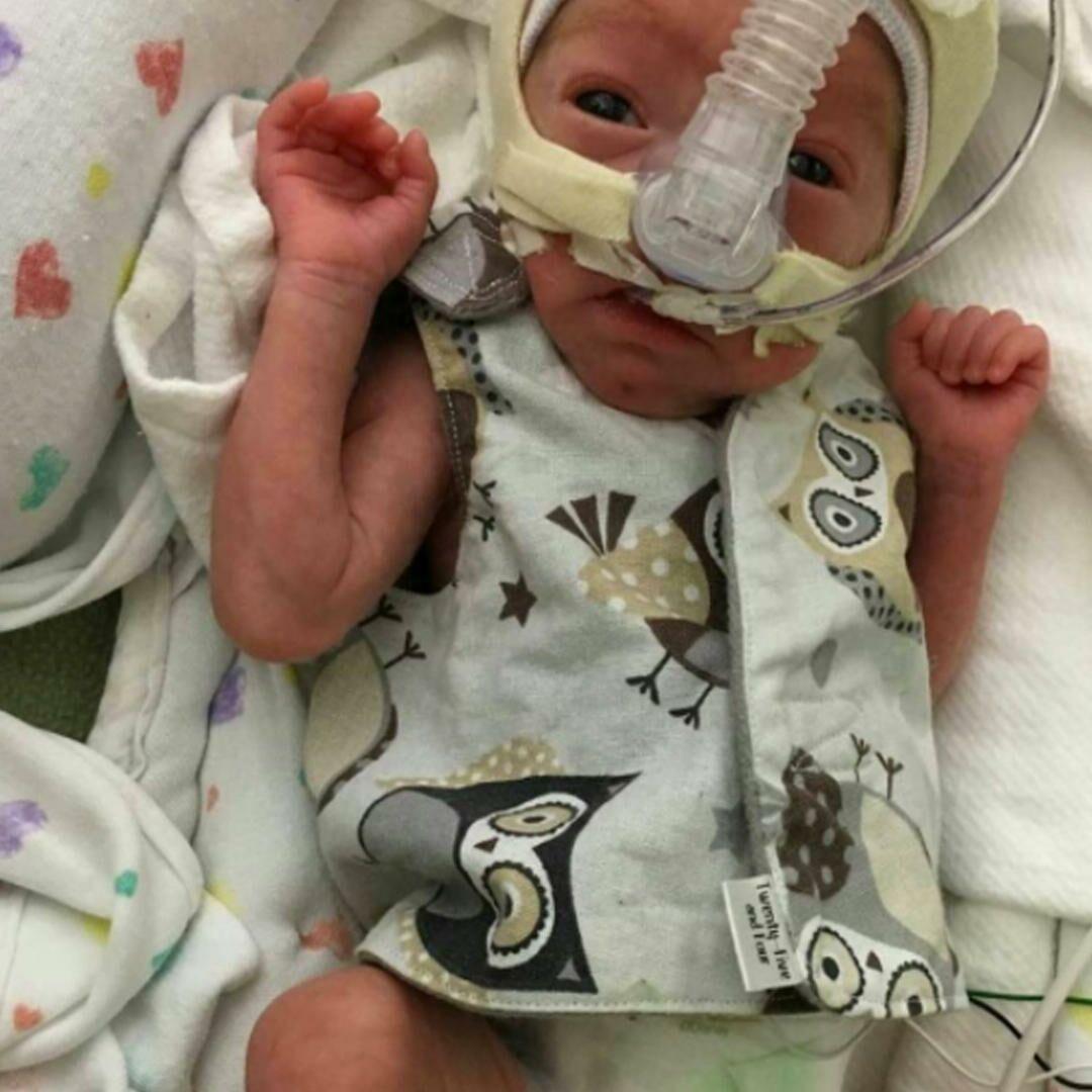 A premature baby wearing an owl shirt